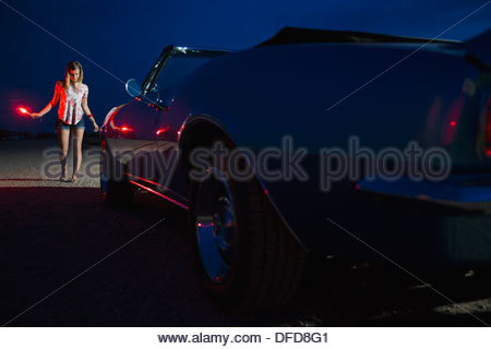 Young woman holding roadside flare near convertible - Stock Photo