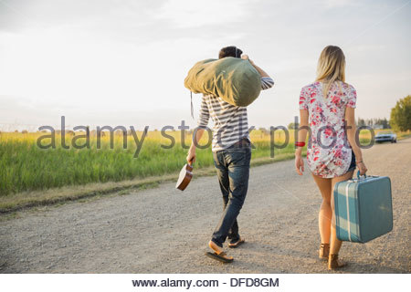 Rear view of young couple with luggage walking on country road - Stock Photo