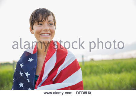 Young woman wrapped in American flag - Stock Photo