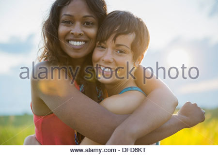Portrait of young women embracing outdoors - Stock Photo