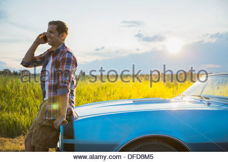 Young man leaning against convertible while talking on cell phone - Stock Photo