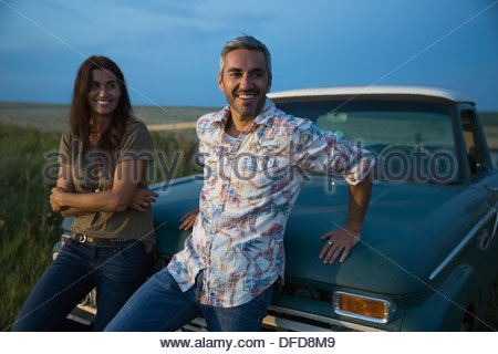 Smiling couple leaning on convertible at dusk - Stock Photo