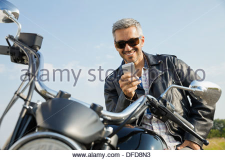 Man sitting on motorcycle and reading smart phone - Stock Photo