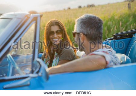 Happy couple on road trip in convertible - Stock Photo