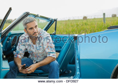 Mid adult man sitting in convertible - Stock Photo