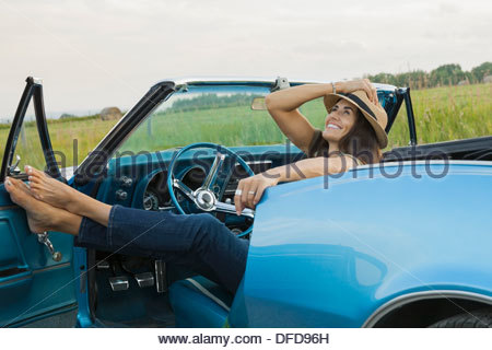 Mature woman relaxing in convertible - Stock Photo