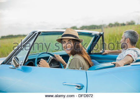 Portrait of couple in blue convertible - Stock Photo