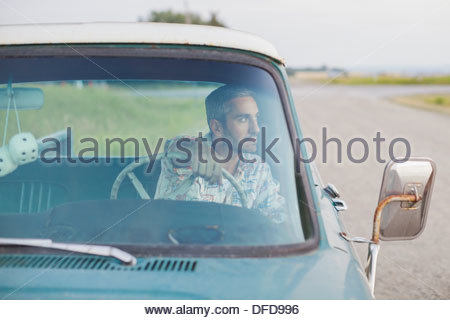 Man sitting in pick-up truck on country road - Stock Photo