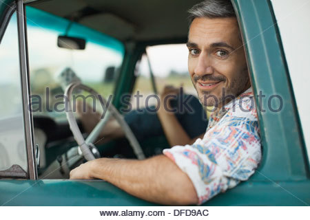 Portrait of mid adult man sitting in pick-up truck - Stock Photo