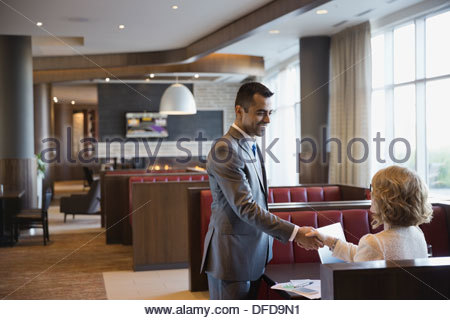 Businessman shaking hands with female colleague in hotel restaurant - Stock Photo