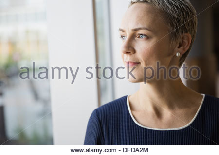 Thoughtful businesswoman looking out window in hotel room - Stock Photo