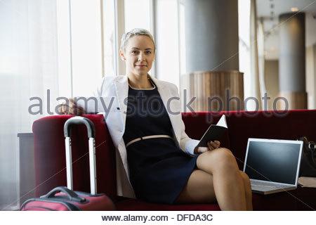 Portrait of confident businesswoman relaxing before flight - Stock Photo
