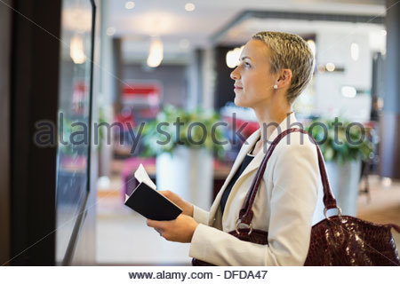 Businesswoman checking schedule at airport terminal - Stock Photo