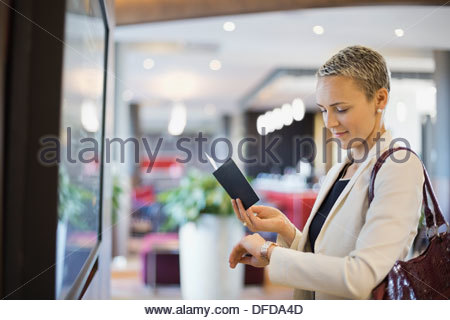 Businesswoman checking the time at airport terminal - Stock Photo