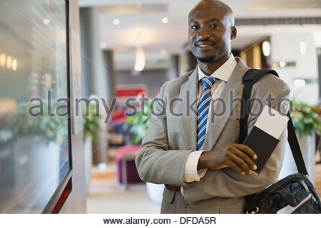 Portrait of confident businessman standing in airport terminal - Stock Photo