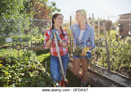Female friends standing together in community garden - Stock Photo