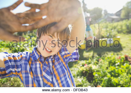 Boy with arms raised standing in community garden - Stock Photo
