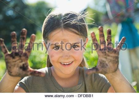 Portrait of little girl showing hands full of dirt - Stock Photo