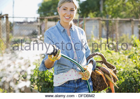 Woman watering plants with garden hose - Stock Photo