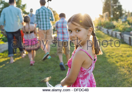 Portrait of cute girl standing with group in community garden - Stock Photo