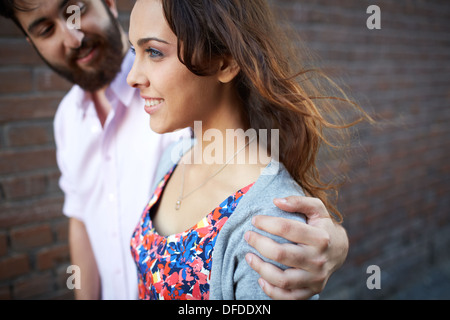 Handsome man embracing young girl while walking outdoors - Stock Photo