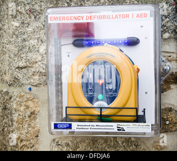 Emergency Defibrillator mounted on wall in a street Mousehole, Cornwall,UK - Stock Photo
