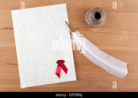 A blank piece of parchment paper with red wax seal, plus feather quill and glass ink well on a desk - Stock Photo