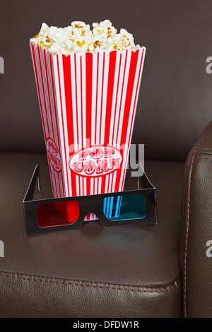 Box of Popcorn with 3D TV glasses on a brown leather home cinema chair. - Stock Photo