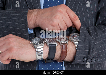 Businessman with four wrist watches checking the time. Good image for time related themes. - Stock Photo