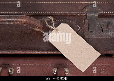 Photo of a blank baggage label on an old brown leather suitcase. - Stock Photo