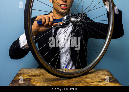 Young businessman is trying to fix a bicycle tire - Stock Photo