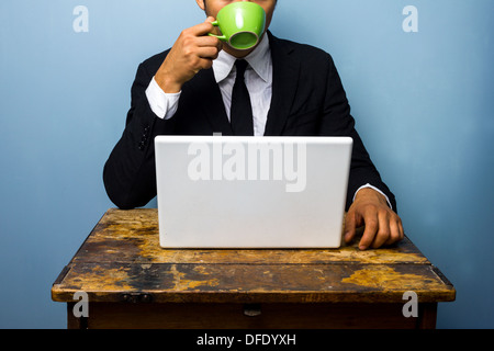 Young businessman is drinking coffee and working on his laptop at an old desk