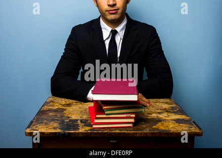 Happy young businessman sitting at an old desk with a stack of books - Stock Photo