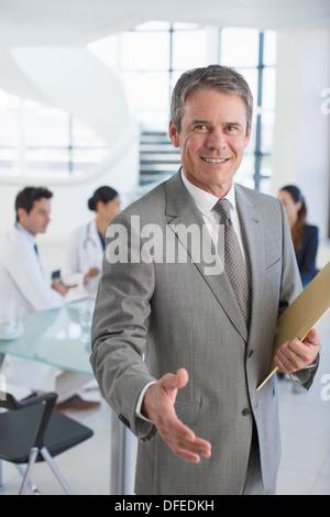 Businessman offering handshake in meeting - Stock Photo