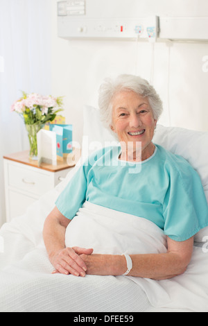 Portrait of smiling aging patient in hospital bed - Stock Photo
