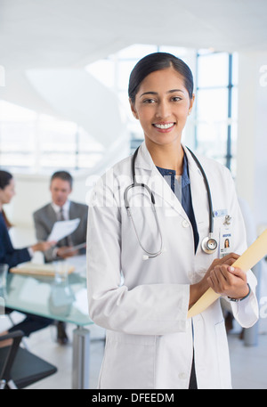 Portrait of smiling doctor in meeting - Stock Photo