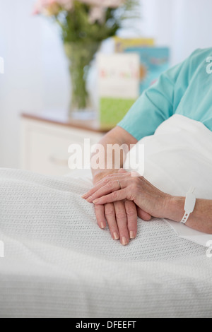 Close up of senior patient's hands in hospital bed - Stock Photo