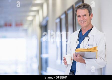 Portrait of smiling doctor in hospital corridor - Stock Photo