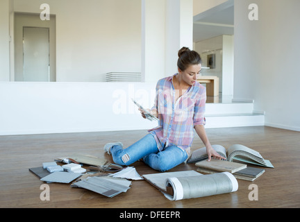 Woman viewing carpet and tile swatches on floor in new house - Stock Photo