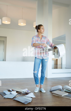 Woman looking at fabric swatches in new house - Stock Photo