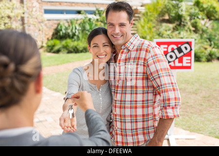 Realtor giving couple keys to new house - Stock Photo