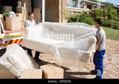 Movers carrying sofa from moving van in driveway - Stock Photo