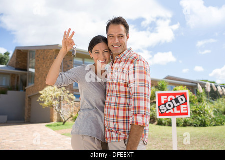 Portrait of smiling couple holding keys in front of new house - Stock Photo