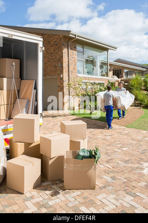 Movers carrying sofa from moving van to new house - Stock Photo