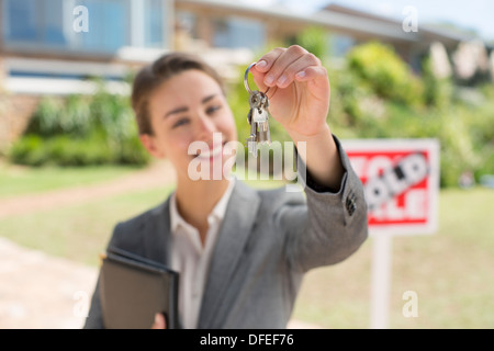 Portrait of realtor holding house keys in front of house - Stock Photo