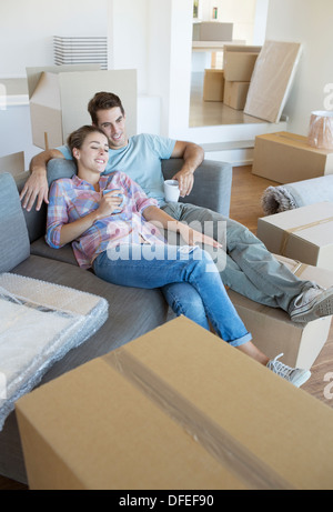 Couple relaxing with coffee on sofa in new house - Stock Photo