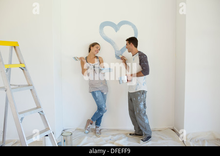 Couple painting blue heart on wall - Stock Photo