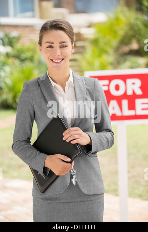 Portrait of smiling realtor near For Sale sign - Stock Photo