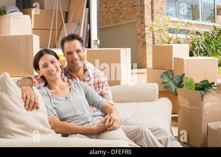 Portrait of smiling couple on sofa near moving van in driveway - Stock Photo