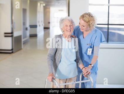 Nurse helping senior patient with walker in hospital corridor - Stock Photo